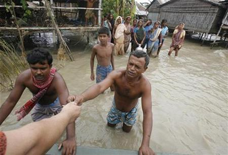 A relief worker gives money to a flood victim in Digrirchar at Rajbari district, 130 km (81 miles) from Dhaka, August 12, 2007. Flood victims in eastern India were eating raw wheat flour to survive as devastating monsoon flooding in South Asia continued to spread misery among millions. REUTERS/Rafiqur Rahman