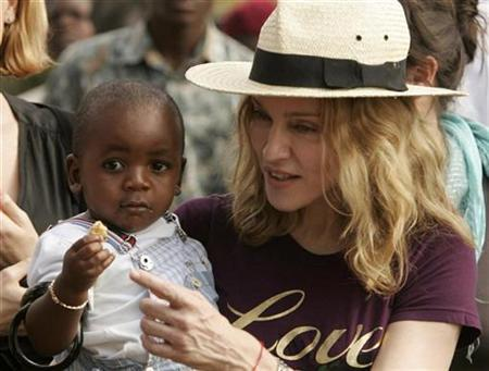 Madonna holds her adopted son, David Banda, at an orphan care centre run by Raising Malawi, a grassroots initiative by Madonna, in Mphendula Village, about 40 km (25 miles) from the capital Lilongwe April 19, 2007. A Malawian court-appointed official said on Monday he will visit Madonna and her husband in early September to access whether they would be suitable parents for the child they are seeking to adopt. REUTERS/Siphiwe Sibeko