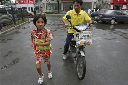 Zhang Huimin (L), 8, runs on a street as her father accompanied her in Beijing August 26, 2007. Zhang arrived in Beijing on Sunday after state media said she ran 3,560 km (2,212 miles) to celebrate the 2008 Olympics, with her father following her all the way on a motorised bicycle. Picture taken August 26, 2007. REUTERS/China Daily