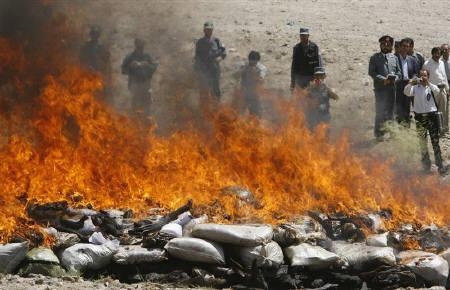 Afghan Interior Ministry officials and police watch a pile seized drugs burning on the outskirts of Kabul August 27, 2007. The U.S. and its allies face a very serious situation battling drug production in Afghanistan, a senior U.S. official said on Wednesday, two days after a U.N. report revealed rampant opium poppy growth. REUTERS/Desmond Boylan