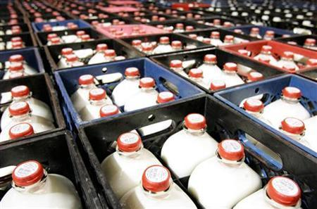 Half-gallon bottles of milk are seen at a distribution centre in a file photo. A drop in milk output due to spiralling farm costs and bad weather has forced Britain's largest dairy farmers' cooperative to invoke ''force majeure'' in cutting supplies to customers in September for the second successive month, the cooperative First Milk said on Wednesday. REUTERS/John Gress