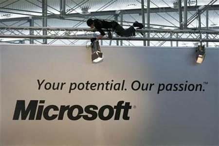 A technician adjusts a spotlight at the exhibition stand of Microsoft in preparation for the CeBIT computer fair in the northern German town of Hanover March 12, 2007. Microsoft Corp <MSFT.O> agreed to acquire Parlano, which provides technology to allow companies to create group chat sessions for employees, and add the application to its portfolio of communication offerings. REUTERS/Christian Charisius