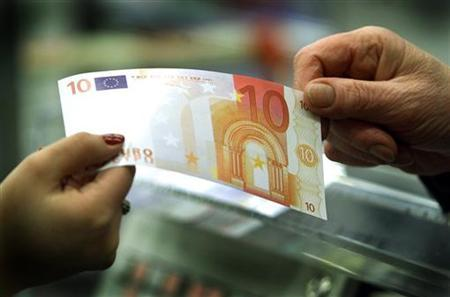A ten euro note changes hands at a supermarket in Muggio on the outskirts of Milan, November 30, 2001. A thief stole a briefcase and threw it away without noticing it contained 10,000 euros ($13,660) in cash, German authorities said Thursday. REUTERS/Stafano Rellandini