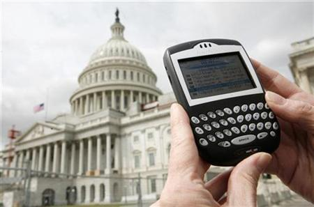 A journalist looks at her Blackberry communication device on Capitol Hill in Washington, April 18, 2007. Research in Motion Ltd shares rose more than 3 percent on Thursday on renewed market speculation that Microsoft Corp could be interested in buying the BlackBerry maker. REUTERS/Jim Young
