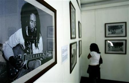 An Ethiopian reggae fan looks at photographs of Bob Marley at an exhibition in Ethiopia's capital Addis Ababa, February 4, 2005. The family of late reggae singer Bob Marley said on Thursday they will sue Universal Music Group and Verizon Wireless for using the iconic pop star's name, likeness and image without permission. REUTERS/Antony Njuguna