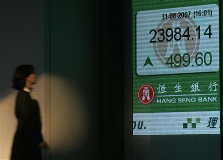 A woman walks past an electronic billboard showing Hang Seng Index in Hong Kong August 31, 2007. REUTERS/Paul Yeung