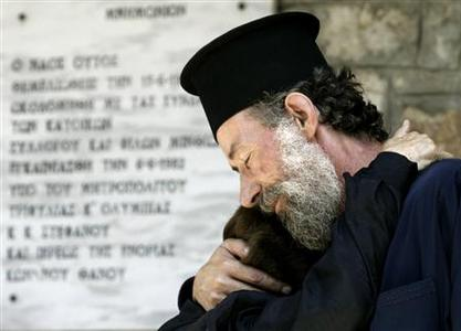 A Greek Orthodox priest hugs a relative of Giorgos Tripodis, who died during last week's forest fires, at Minthi village some 370 km (230 miles) southwest of Athens August 31, 2007. REUTERS/Yiorgos Karahalis