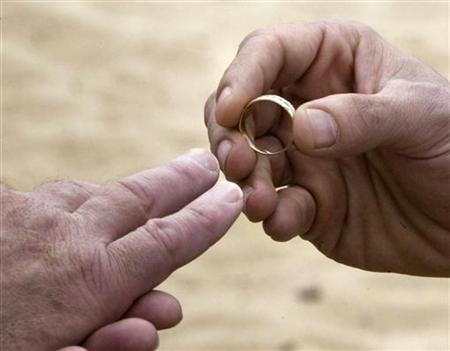 A man puts a wedding ring on his partner's finger in a file photo. Gay couples lined up before dawn on Friday to apply for marriage licenses after an Iowa judge scuttled the state's law against same-sex marriage. REUTERS/Brian Snyder