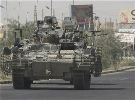British armoured vehicles patrol a road near the scene of an attack on a fuel truck in Basra May 21, 2007. British troops are pulling out of a base at a palace in the southern Iraqi city of Basra on Sunday, a Ministry of Defence source said. REUTERS/Atef Hassan