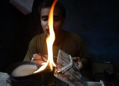 A silversmith makes ornaments at a roadside workshop in the eastern Indian city of Kolkata August 29, 2007. The silver jewellery industry is made up of high-end fashion jewellery, also called sterling jewellery accounts for about 20 to 30 percent. REUTERS/Parth Sanyal