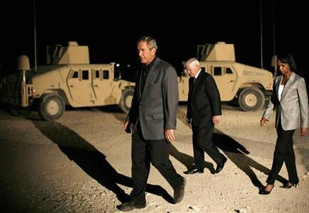 President George W. Bush walks in front of Humvees with Defense Secretary Robert Gates and Secretary of State Condoleezza Rice following remarks to the press after nightfall at Al-Asad airbase in Anbar Province September 3, 2007. REUTERS/Jason Reed