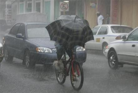 A man rides a bicycle in the rain along a street in the city port of La Ceiba, Honduras, September 4, 2007. REUTERS/Daniel Aguilar