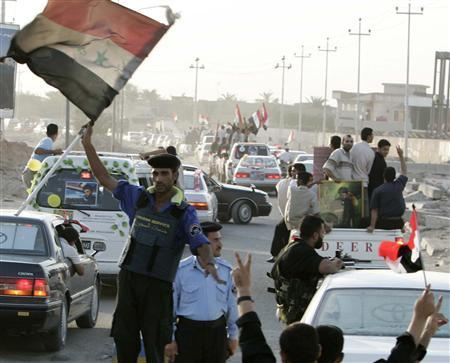 A policeman waves a flag as supporters of Shi'ite cleric Moqtada al-Sadr celebrate in the streets in Basra, south of Baghdad, September 7, 2007. Hundreds of supporters of Shi'ite cleric Moqtada al-Sadr took to the streets on Friday, celebrating the British handover of presidential palaces to the Iraqis . REUTERS/Atef Hassan