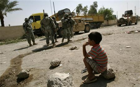 An Iraqi boy watches U.S. soldiers as they arrive to a patrol in Zafraniya neighbourhood, southeast of Baghdad, September 7, 2007. REUTERS/Carlos Barria