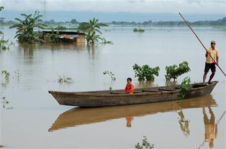 A father and child travel on a boat in the flooded Kokormara village, about 55 km (34 miles) west of Guwahati, the major city of India's north eastern state of Assam, September 9, 2007. Rains have triggered fresh floods in the Indian states of West Bengal, Bihar, Uttar Pradesh, Assam, Meghalaya and Arunachal Pradesh, officials said. REUTERS/Utpal Baruah