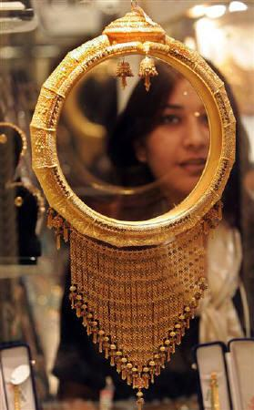 A woman looks at a gold ornament at Vivaha '06'', a travelling wedding exhibition, in Kolkata August 7, 2006. REUTERS/Jayanta Shaw/Files