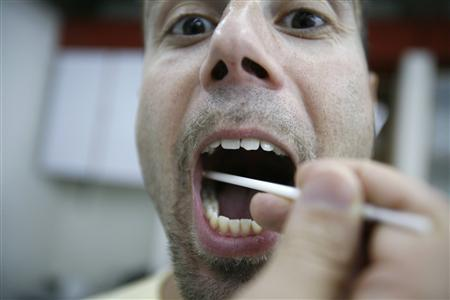 Lebanese geneticist Pierre Zalloua takes a saliva sample form a Lebanese man to test his DNA in a university laboratory near Byblos ancient city in north Lebanon, in this August 17, 2007 file photo. Zalloua following the genetic footprint of the ancient Phoenicians says he has traced their modern-day descendants, but stumbled into an old controversy about identity in his country. REUTERS/Jamal Saidi/Files