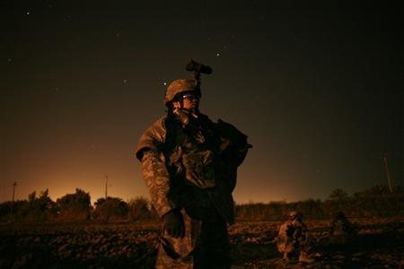 A U.S. soldier of Bravo company, 2nd Battalion, 17th Field Artillery Regiment stands in an open area during a night operation at Zafraniya neighborhood in Baghdad, September 8, 2007. REUTERS/Carlos Barria