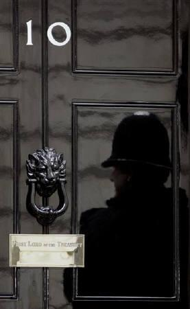 A policeman is reflected in the door of number 10 Downing Street in London in this May 17, 2007 file photo. REUTERS/Luke MacGregor