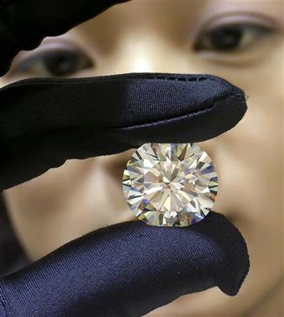 A saleswoman displays a 26.62 carat diamond at a shopping centre in Nanning, south China's Guangxi province November 27, 2006. About 70 percent of Chinese regard the wealthy as immoral and unworthy of respect, according to a survey in the world's biggest Communist state. REUTERS/China Daily