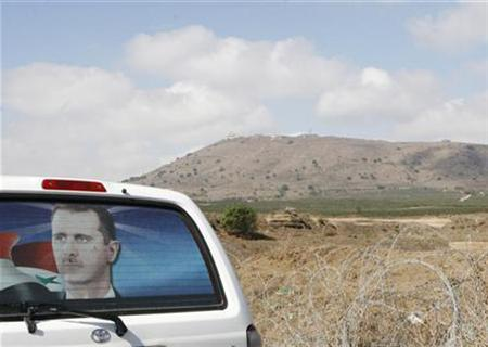 A Syrian car with a poster of Syrian President Bashara al-Assad parks opposite an Israeli military post on the occupied Golan Heights, September 6, 2007. REUTERS/Khaled al-Hariri