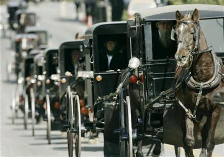 (R) leads a funeral procession of Amish mourners near Lancaster, Pennsylvania, October 5, 2006, on the way to a cemetery to bury young Naomi Rose Ebersole. The Amish community that lost five girls in a Pennsylvania schoolhouse shooting massacre last year has donated money to the widow of the gunman, the community said on Wednesday. REUTERS/Jason Reed