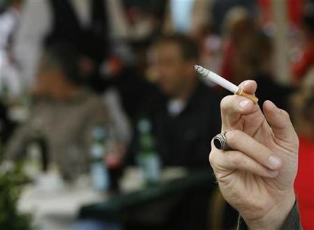 A smoker holds a cigarette in a public place near the Stade de Geneve in Geneva August 22, 2007. ndonesian authorities plan to offer prostitutes in a key cigarette producing area jobs after it banned them from soliciting during the holy Muslim month of Ramadan, a newspaper said on Friday. REUTERS/Denis Balibouse