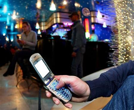 A man uses a cellular phone in a Milan bar March 3, 2006. Media and advertising companies have found a way of latching on to people's handsets by beaming ads to them via Bluetooth, the same technology used in some hands-free headsets. REUTERS/Daniele LA Monaca