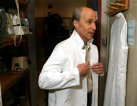 Stanford University professor Roger Kornberg puts on a lab coat in his office in Stanford, California October 4, 2006. REUTERS/Dino Vournas