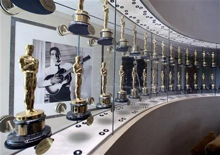 A photograph of the late singer and actor Elvis Presley is framed by a portion of the Academy Awards bestowed upon films from movie studio Metro-Goldwyn-Mayer Inc. on display at the studios Los Angeles office, March 8, 2006. MGM unveiled plans on Tuesday to launch a high-definition television channel this fall on the DirecTV satellite service with a mix of movies and original programs. REUTERS/Fred Prouser