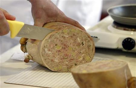 A man cuts through a sausage in Germany in a file photo. Staff at a German butcher's shop were shocked to discover a customer had hidden two sex toys in their sausages for transport to Dubai, police said Wednesday. REUTERS/Alex Grimm