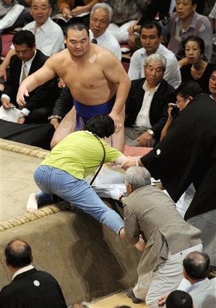 Sumo wrestler Takamisakari (C), judges and bystanders restrain a woman attempting to climb into the sumo ring during the Autumn Grand Sumo Tournament in Tokyo on September 19, 2007. The woman invaded a sumo ring -- a sacred arena from which females are banned -- in Tokyo during a major tournament, domestic media said on September 20, 2007, then was pulled down by a referee and one of the sport's huge wrestlers. REUTERS/Kyodo
