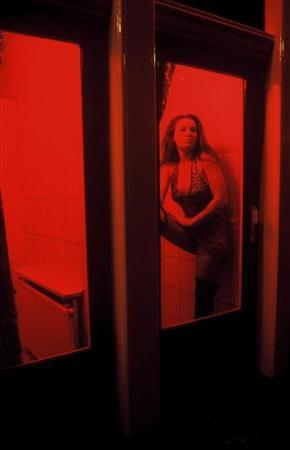 A Dutch prostitute sits behind her window in the red light district in Amsterdam, The Netherlands January 26, 2006. About a third of Amsterdam's red-lit windows for prostitutes will disappear from the city center as one of the main brothel owners is set to sell his empire to a real estate company. REUTERS/Jan Kees Helms