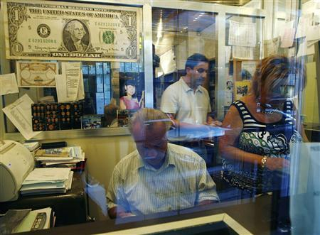 An enlarged copy of a U.S. dollar hangs on the wall above employees at a currency exchange in Paris September 20, 2007. The euro hit a record high against the dollar breaking above $1.40 per euro for the first time, weakened by a hefty U.S. interest rate cut this week and expectations of further cuts in benchmark rates. REUTERS/John Schults