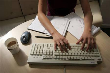 A generic picture of a woman working in an office typing on a computer. REUTERS/Catherine Benson