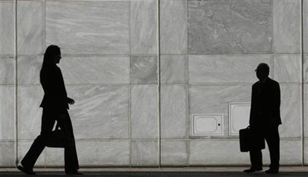 People are silhouetted at Canary Wharf business district in London May 1, 2007. Forbes has spent nearly a century covering businessmen clad in Brooks Brothers shirts and gray flannel suits. Now the magazine empire is aiming at executives who prefer Prada skirt suits and Balenciaga pumps. REUTERS/Luke MacGregor