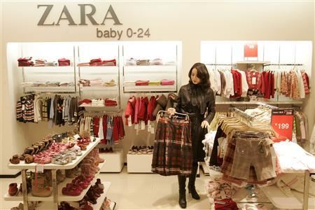 A customer looks at outfits at a Zara shop in Shanghai January 9, 2007. REUTERS/Aly Song