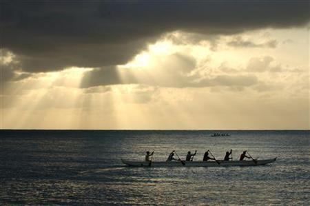 Sun shines over outrigger paddlers practicing on the North Shore of the island of Oahu, in Haleiwa, Hawaii, June 15, 2006. Delegates from almost 200 countries agreed late on Friday to eliminate ozone-depleting substances faster than originally planned, the United Nations said. The earth's ozone layer protects the planet from the sun's ultraviolet radiation. REUTERS/Lucy Pemoni