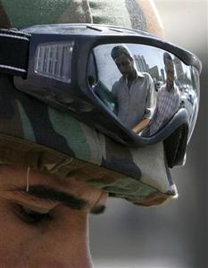 A member of the Special Police Commandos searches residents at a checkpoint in Baghdad September 23, 2007. EUTERS/Ceerwan Aziz