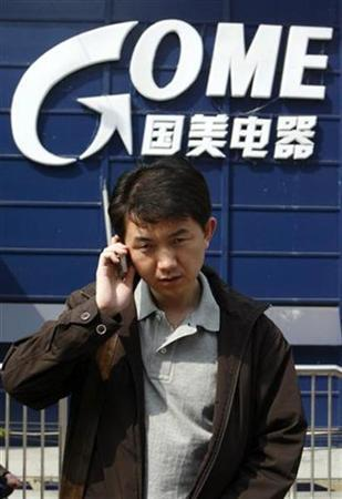 A man talks on his mobile phone as he walks past a GOME Electrical Appliances store in Beijing, April 18, 2007. Dell Inc said on Monday it would sell its latest range of personal computers through China's largest electronics retailer, GOME Group, aiming to improve on its single-digit mainland market share. REUTERS/Claro Cortes IV