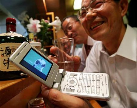 Mitsuo Nishigaki shows off his TV cellphone at a Japanese pub in Tokyo July 4, 2006. Europeans' interest in watching mobile television is as tiny as cellphone screens, a new study showed on Monday, even though the industry has been buzzing about offering TV on handsets for years. REUTERS/Toru Hanai