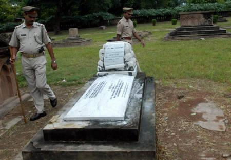 Police walk near the grave of a British soldier at the Residency in Lucknow September 24, 2007. A group of retired British soldiers and civilians visiting India have caused outrage during their trip to pay homage at sites where British soldiers died during the 1857 revolt against colonial rule. REUTERS/Pawan Kumar