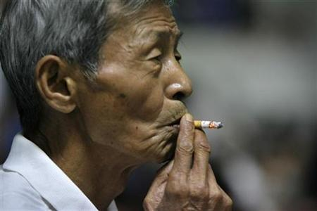 A man smokes a cigarette in east China's Jiangsu province, September 12, 2007. Cancer deaths will more than double to 17 million people each year in 2030 with poor countries shouldering the heaviest burden from the disease, the head of the United Nation's cancer agency said on Monday. REUTERS/Sean Yong