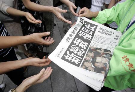 9月25日、23日の自民党総裁選で福田康夫元官房長官が新総裁に当選、25日の国会で首相指名を受け、福田内閣を発足させる。写真は23日都内で、号外に手をのばす人々(2007年 ロイター/Yuriko Nakao)