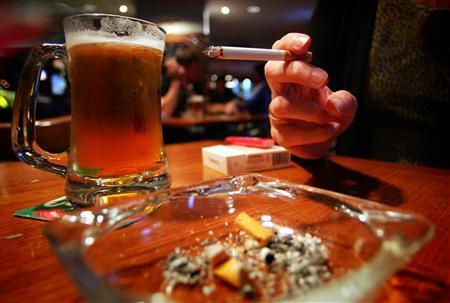 A drinker in an inner Sydney bar smokes while enjoying a beer October 13, 2004. REUTERS/Tim Wimborne