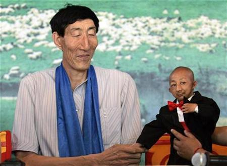 He Pingping (R), 19, a 0.73 metres (2 feet, 5 inches) man, adjusts his suit as he shakes hands with Bao Xishun (L), 56, a 2.36-metre (7 feet, 9 inches) herdsman listed by the Guinness World Records as the tallest living man, in Baotou, north China's Inner Mongolia Autonomous Region July 13, 2007. REUTERS/Jason Lee