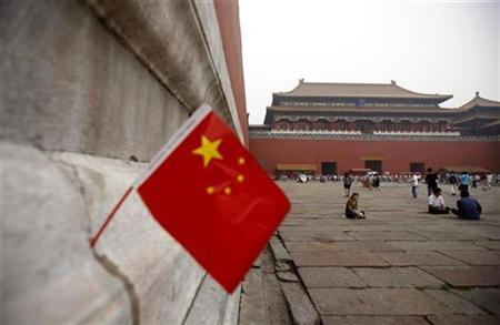 A Chinese flag, placed in a wall, can be seen as tourists sit in front of the Meridian Gate, the entrance to the Forbidden City, in Beijing August 5, 2007.China has banned ''sexually provocative sounds'' on television and pulled the plug on a show reconstructing infamous crimes by women ahead of a major Communist Party meeting next month. REUTERS/David Gray