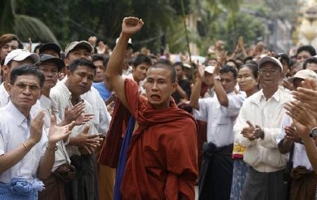 A monk rallies others to join in an anti-government march as bystanders clap and cheer them in Yangon September 24, 2007. REUTERS/Stringer