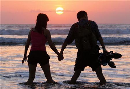 A couple watches the sun set at Kuta beach on Bali October 3, 2005. The risk of divorce increases if one partner suffers from testicular or cervical cancer, but other types have no effect on whether a couple stays together, Norwegian researchers said on Thursday. REUTERS/Luis Ascui