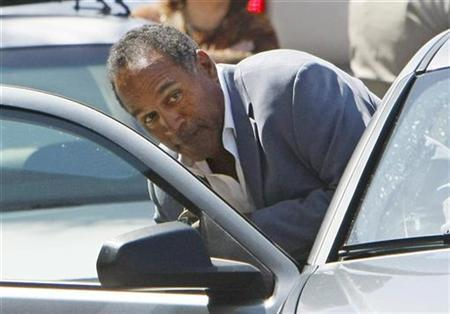 Former NFL football star O.J. Simpson ducks into a car outside the Clark County Detention Center in Las Vegas, Nevada September 19, 2007 after being released from jail on bail of $125,000. REUTERS/Rick Wilking